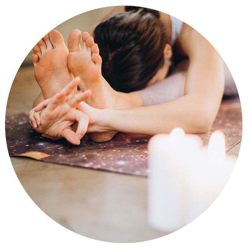 A woman sits in a yoga pose with candles