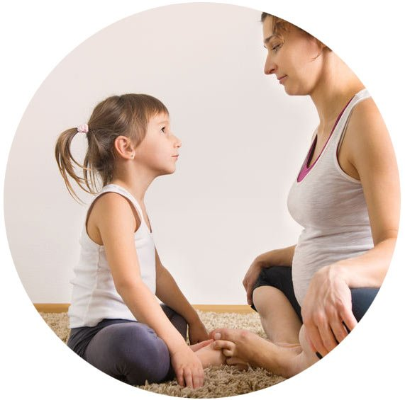 A mother and daughter sit facing one another in a yoga pose