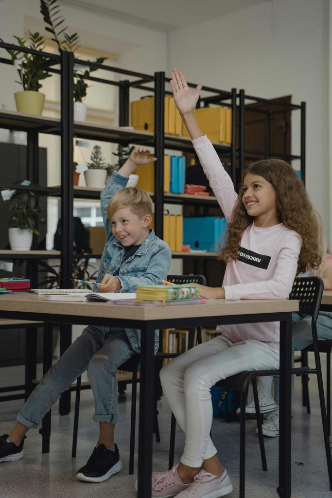 Two young kids sit at a desk and raise their hands